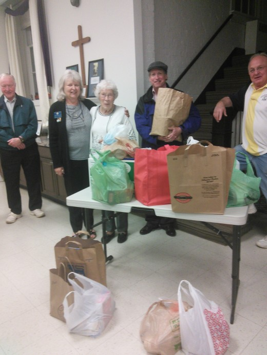 Lions present dry goods they collected to Olney Help representative Marilyn Simonds