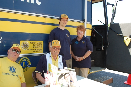 Lions Bill Thomas, Don Beeson, Greg Fuller, and Ann Bucher pose outside the Lions Community Outreach Foundation Mobile Health Unit